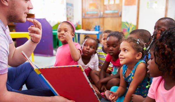 Ein junger Mann unterrichtet kleine Kinder in Afrika
