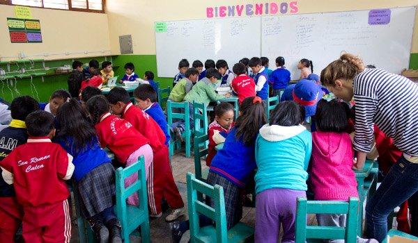 Viele peruanische Kinder sitzen in Gruppen in einer Schulklasse
