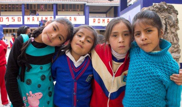 vier peruanische Kinder stehen auf dem Pausenhof ihrer Schule