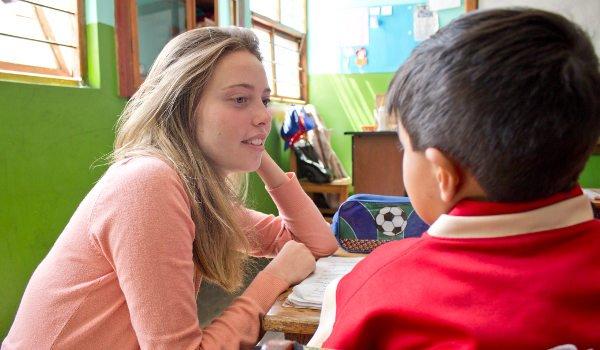 Ein junges Mädchen sitzt in einer Schule in Südamerika und unterrichtet einheimische Kinder